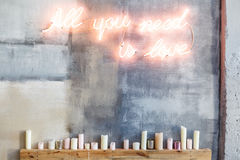 Neon inscription `All you need is love`. On a grey concrete wall and many candles under them Royalty Free Stock Images