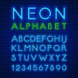 Neon latin alphabet. Blue neon light glowing latin alphabet and digits against a brick wall background. Vector illustration Royalty Free Stock Photo