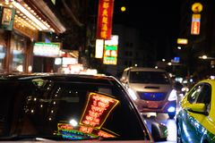 Neon light signs reflect on windscreen of car in Yaowarat road a royalty free stock image