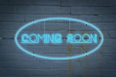 Neon-lighton die Wand mit dem Wort, das BALD KOMMT stockfotografie