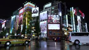 Neon lights and billboard advertisements on buildings at Akihabara at rainy night, Tokyo, Japan stock footage