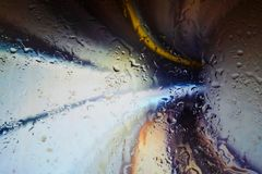 Neon lights behind water drops close up inside tunnel speed lights stock photo