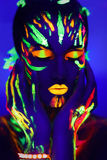 Neon make up art glowing painting. Woman's face with fluorescent make up art. Blue background. Studio shot. Orange, green, yellow neon paints. Creative idea is Stock Images
