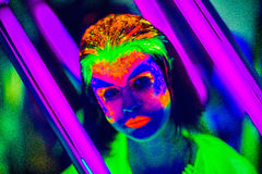 Neon Make Up. Woman's face with fluorescent make up art. Blue background. Studio shot. Orange, green, pink neon paints. Creative idea is good for clubs, disco Stock Photography