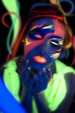 Neon Make Up. Woman's face with fluorescent make up art. Blue background. Studio shot. Orange, green, yellow neon paints. Creative idea is good for clubs, disco Royalty Free Stock Photography