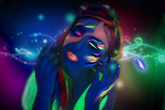 Neon Make Up. Woman's face with fluorescent make up art. Blue background. Studio shot. Orange, green, yellow neon paints. Creative idea is good for clubs, disco Stock Images