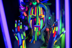 Neon Make Up. Woman's face with fluorescent make up art. Blue background. Studio shot. Orange green yellow neon paints. Creative idea is good for clubs, disco Stock Photos