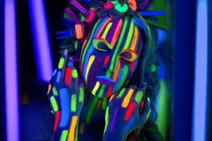 Neon Make Up. Woman's face with fluorescent make up art. Blue background. Studio shot. Orange, green, yellow neon paints. Creative idea is good for clubs, disco Royalty Free Stock Images