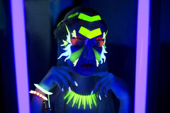 Neon Make Up. Woman's face with fluorescent make up art. Blue background. Studio shot. Orange, green, yellow neon paints. Creative idea is good for clubs, disco Stock Photography