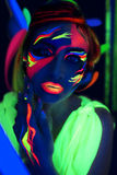 Neon Make Up. Woman's face with fluorescent make up art. Blue background. Studio shot. Pink green yellow neon paints. Creative idea good for clubs, disco, go-go Stock Photos