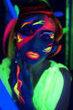 Neon Make Up. Woman's face with fluorescent make up art. Futuristic background. Studio shot. Orange, green, pink neon paints. Creative idea is good for clubs Royalty Free Stock Images