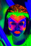 Neon Make Up. Woman's face with fluorescent make up art. Futuristic background. Studio shot. Orange, green, pink neon paints. Creative idea is good for clubs Stock Image