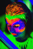 Neon Make Up. Woman's face with fluorescent make up art. Futuristic background. Studio shot. Orange, green, pink neon paints. Creative idea is good for clubs Royalty Free Stock Photography
