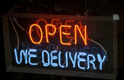 Neon Mistake. A sign in neon in a restaurant window with a grammar mistake that should say we deliver or just delivery Stock Image