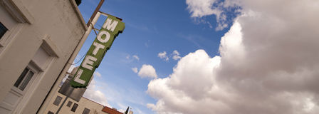 Neon Motel Sign Clear Blue Sky White Billowing Clouds Stock Photo