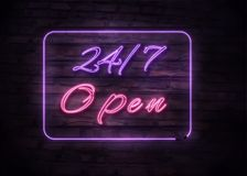 Neon Open 24/7 sign on brick wall background. Realistic glowing neon inscription. Open 24 Hours Royalty Free Stock Image
