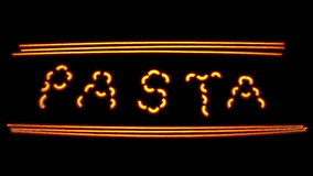 Neon pasta. Fun and pretty unique pasta word neon sign concept where letters are made of macaroni and spaghetti pasta. Isolated on black background Royalty Free Stock Images