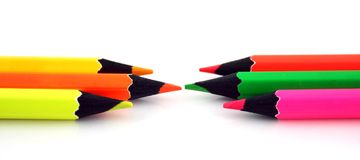 Neon pencils facing each other. On a white background Royalty Free Stock Image