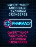 Neon pharmacy glowing signboard with two different colors alphabets. Illuminated drugstore sign open 24 hours. Neon pharmacy glowing signboard with two Stock Photo