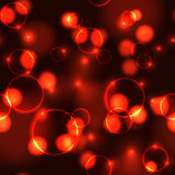 Neon red bokeh effect seamless pattern. Dark background with Glowing sparkling circles and rings in hot colors Stock Image