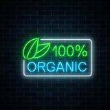 Neon segno di produzione organica di 100 per cento sul fondo scuro del muro di mattoni Simbolo d'ardore di pubblicità dei cosmeti Immagine Stock