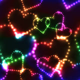 Neon shinning colorful hearts on dark background Royalty Free Stock Photography