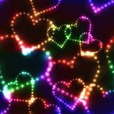 Neon shinning colorful hearts on dark background. Neon shinning rainbow colorful hearts on dark background - seamless background Royalty Free Stock Photography