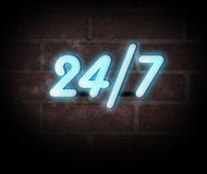 Neon Sign 24 7. Blue neon sign on a brick wall with message 24/7 royalty free stock photo