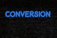 Neon sign on brick wall - CONVERSION. Blue Neon Sign on dark brick wall - CONVERSION stock photos