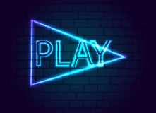 A neon sign in button to play against a brick wall. Royalty Free Stock Photos