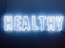 Neon sign caligraphy with the word healthy spelt out. Blue white letters royalty free stock images