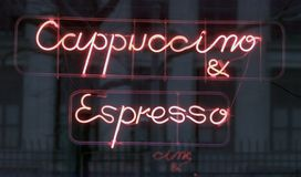 Neon sign (cappuccino & espresso) outside a cafe. Neon sign advertising coffee (cappuccino & espresso) in the window of a cafe with reflection of buildings Royalty Free Stock Image