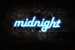 Neon Sign Midnight. Blue neon sign on a stone wall with message midnight stock images