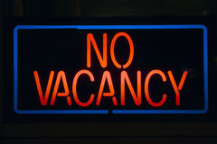 Neon sign reads No Vacancy. For a motel at night stock photos