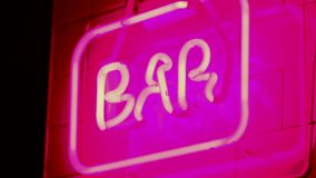 Neon sign saying BAR nightlife angled close shot. Bars and pubs. Red and pink stock video footage
