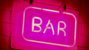 Neon sign saying BAR nightlife angled close shot. Red and pink stock footage
