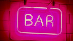 Neon sign saying BAR nightlife straight shot. Bars and pubs. Red and pink stock video