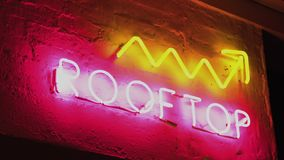 Neon sign saying Rooftop Upstairs nightlife side shot. Pink and yellow stock video