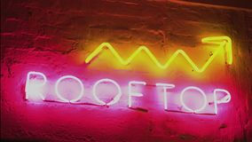 Neon sign saying Rooftop Upstairs nightlife straight shot stock footage