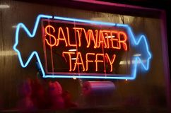 Neon Saltwater Taffy. A neon sign in a store window at night at the New Jersey seashore advertises that the local speciality saltwater taffy is sold within stock photography