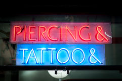 Neon signboard with Piercing & Tattoo at night. Stock Photography