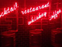 Neon signs and barrel urinals in a pub in Shanghai. Attached to a micro brewery, the gents toilets in this Shanghai boozer featured a neon red glow stock photo