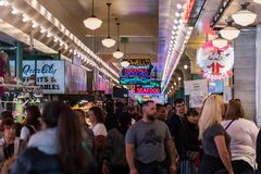 Neon signs and people inside the Pike Market in Seattle, Washington, USA royalty free stock image