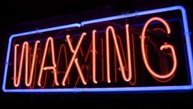 Neon Spa Waxing sign. Red and Blue WAXING Sign lights up the night Royalty Free Stock Photography