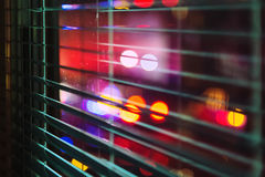 Neon Spot Lights through Window Blind. Bright colored spot lights shining through an open window blind at night Stock Photography