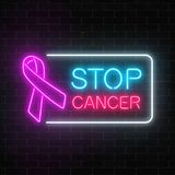 Neon stop cancer glowing sign on a dark brick wall background. Pink ribbon as a cancer awareness month. Royalty Free Stock Photography