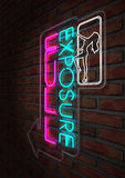 Neon Stripper Sign on A Face Brick Wall. An illuminated neon sign for a strip club mounted on a brick wall incorporating an arrow, a dancing girl and the words stock photos
