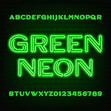 Neon tube alphabet font. Purple type letters and numbers on a dark background. Royalty Free Stock Image