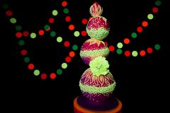 Neon UV photography bright colorful wedding cake glows fluorescent colors on a dark background in the rays of stock images