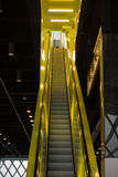 Neon yellow escalator. Up escalator with darker surroundings Stock Images